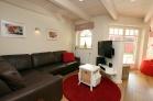 Wohnzimmer mit Ledercouch und LCD/TV